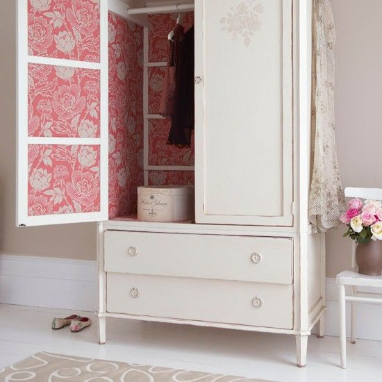 Lined with coral toned damask wallpaper, this painted wardrobe has a dramatic feel when the doors are open, and will complement a spacious bedroom