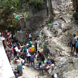 Hard to see, but a reality in Haiti every day; people collecting water from street runoff.