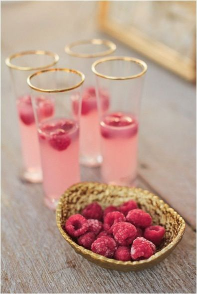 Place frozen raspberries in these gold rimmed glasses of champagne to create a whimsical cocktail.