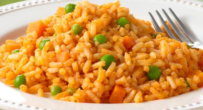 Authentic Mexican rice has a distinctive red-orange color and a ...