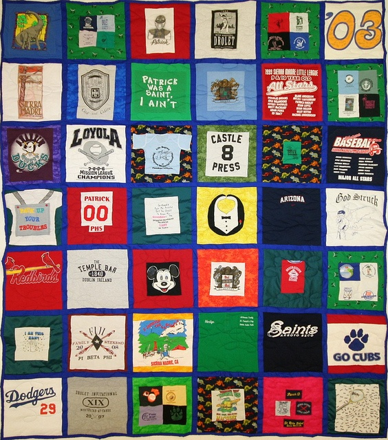This 42-square quilt is amazingly colorful! The owner opted to have a lot of her shirts cut smaller and then appliqued on to vibrant squares of fabric that she provided. And the wee squares just make it plain adorable!