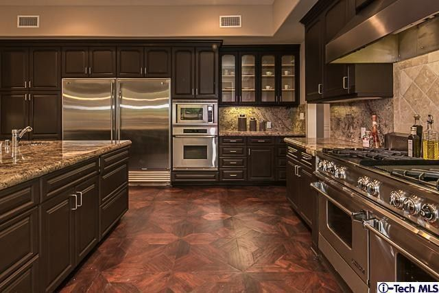 Wide open kitchen with dark chocolate brown cabinets All stainless