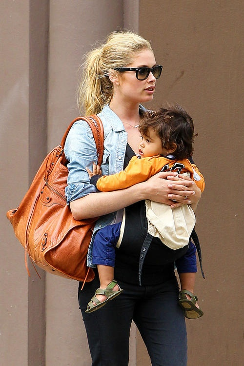 Victoria's Secret Angel Doutzen Kroes holds on tightly to her son Phyllon Joy Gorre as they walk around New York City