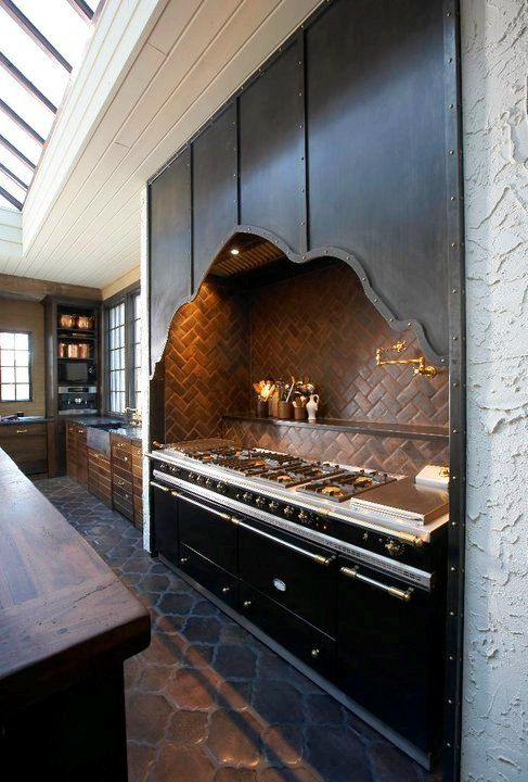 Kitchen stove area with metal curved surround covering the hood.  LOVE this!