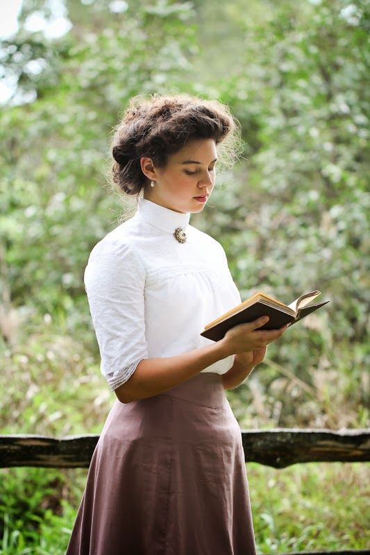 "Lady Emily reading ""The Lady of Shalott"" in her outfit inspired by Anne of Green Gables. Dress by Tara Janelle, lassofyesteryear.com.  On either side the river lie Long fields of barley and of rye, That clothe the wold and meet the sky; And thro' the field the road runs by            To many-tower'd Camelot; And up and down the people go, Gazing where the lilies blow Round an island there below,            The island of Shalott.  Love the dress!"