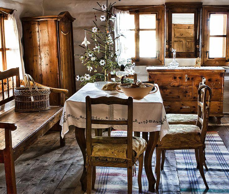 Casa de campo com decoração rústica, móveis de madeira, toalha delicada e arranjo de flores