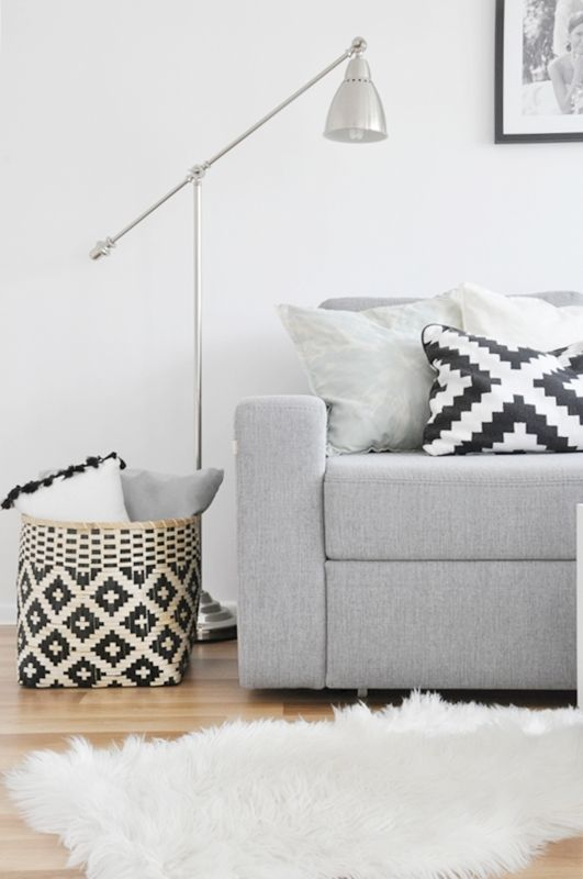 Gray couch with black, white, and gray throw pillows. Basket, sheepskin rug, #IKEA barometer lamp. ❋