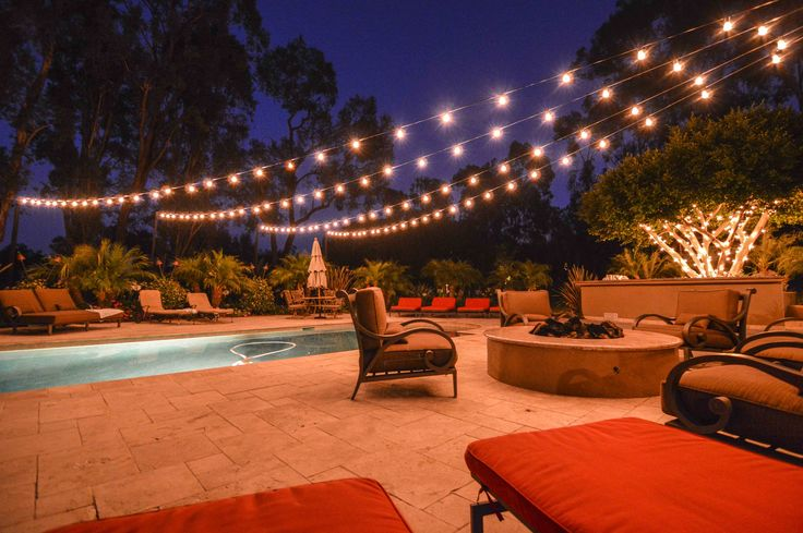 Market lights at a backyard wedding in a starburst display over a pool. Market Lights String ...