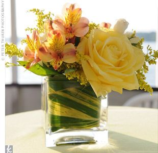 Thick leaves lined short, square vases filled with roses, alstromeria, and accent blooms.