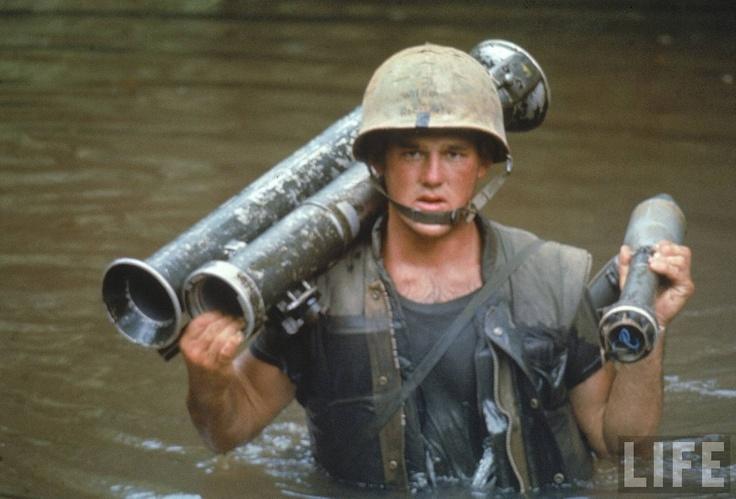 US Marine Phillip Wilson carrying rocket launcher across stream during fighting near the DMZ during the Vietnam War.