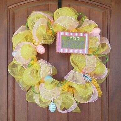 """Yellow mesh, pink ribbon, green tubing curls.  Little Easter eggs, and glittery metal """"Happy Easter"""" sign"""