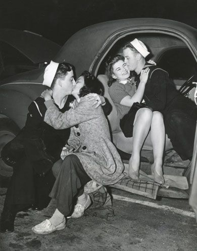 """""""Parting is such sweet sorrow"""" -- These Navy couples make the best of their final moments together before the Middies shove off for their six weeks of war maneuvers in the Pacific with the U.S. Fleet."""" San Pedro, Ca, April 2, 1940."""