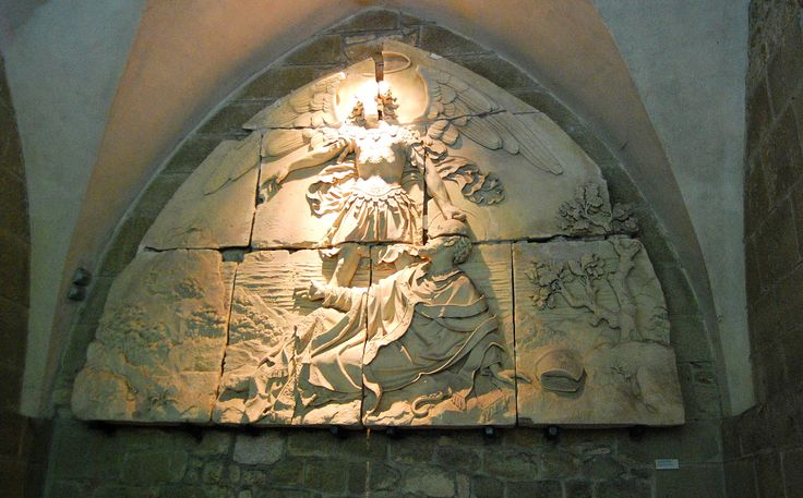 the archangel Michel (Michael) touching the head of the bishop, burning a mark into his forehead. ( Mont St. Michel )