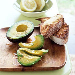 Spread ripe avocado seasoned with lemon, olive oil and sea salt on ...