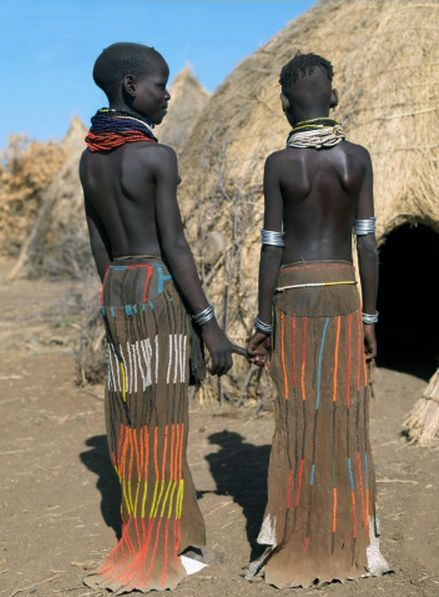 Africa | Two Nyagatom girls wear eye-catching decorated leather skirts outside their family home. Omo Valley, southwest Ethiopia | ©Nigel Pavitt