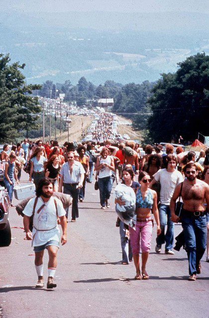 August 1969, Crowds of people carry picnic and camping supplies while walking past parked cars on the road to the Woodstock Music Festival in Bethel, New York. -- Epic Rights along with Perryscope Represents Woodstock for Branding and Licensing