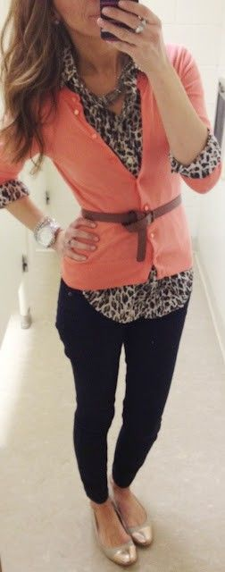 Coral cardigan over animal blouse with black pants.