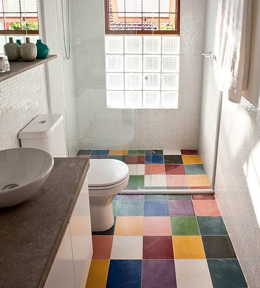 O banheiro tem base branca, mas divertido mosaico de cores dos ladrilhos hidráulicos no piso. Projeto comandado pela arquiteta Fernanda Neiva