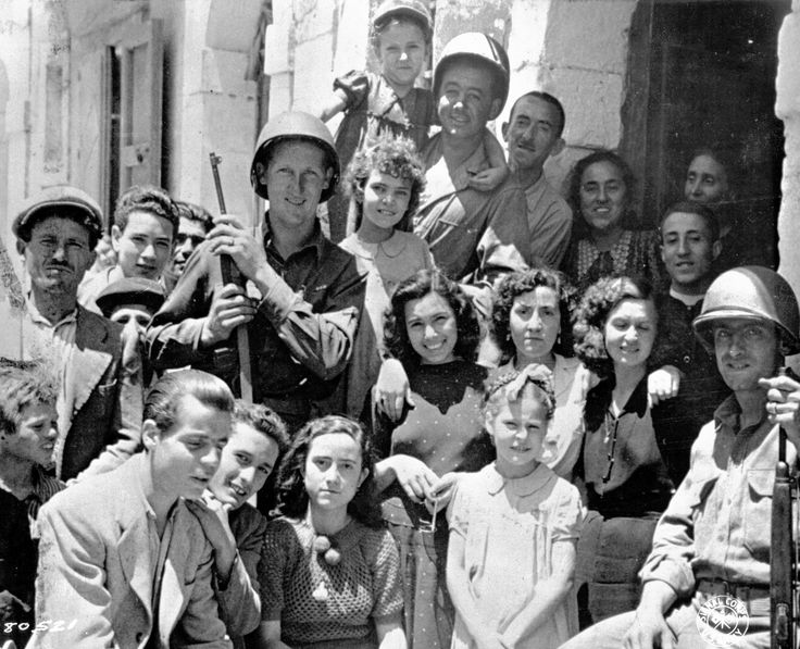 US Army Private George Katere, Private First Class William Mosa, and Private First Class Jessie Hampton posing with Sicilian civilians, Italy, 11 Jul 1943.