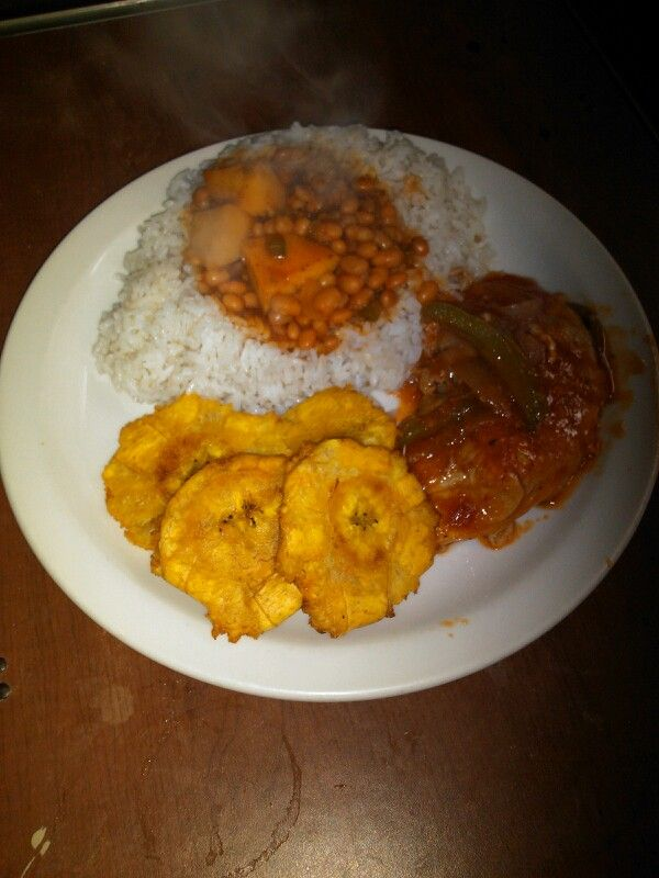 White rice with white beans some tostones and pork chop in salsa(stew ...