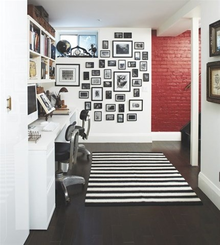 Embrace brick walls instead of drywalling over them. A red accent wall adds the appearance of depth to this basement and feels bold and cheerful in contrast with the simple black and white scheme.