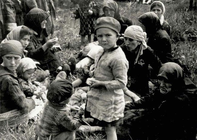 """Jews who had just undergone selection at Auschwitz-Birkenau and were classified as """"not fit for work"""" in a grove before being gassed. The undressing rooms of the crematorium were not sufficient to handle the vast numbers of Hungarian Jews arriving daily in the summer of 1944. Many had to wait in the grove beside the crematorium, exhausted and in a state of shock from the horrors of the journey and the selection process that they had just endured. Most had no idea what fate awaited them"""