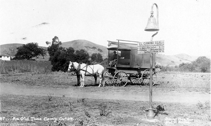 """An old time camp outfit near Ventura Boulevard and Valley Circle Boulevard, circa 1900. Leonis Adobe is in the background. On the El Camino Real sign it says, """"83.9 Santa Barbara, 18 Newberry Park, 47.9 Ventura, Los Angeles 26.1, Encino 8, Hollywood 19.6, San Fernando Mission 14. The El Camino Real bells were placed along the mission routes. """" West Valley Museum. San Fernando Valley History Digital Library."""