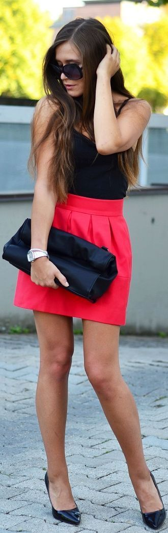 Bright pink high waisted skirt with black top and black heels