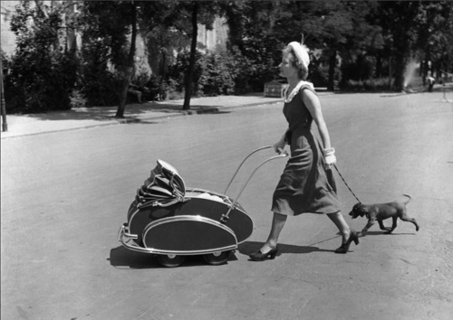 Une femme avec un landau et un chien traversant la Ahornstrasse, 1950    by Friedrich Seidenstücker