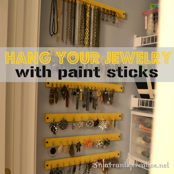 Hanging jewelry organizer using paint sticks and cup hooks.