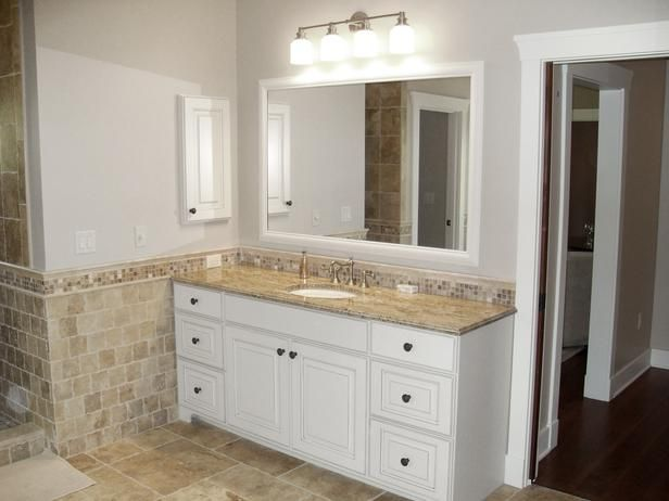 transitional bathroom with white cabinetry and tile wainscot