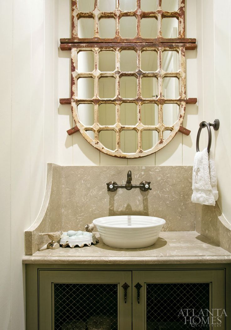 Great powder room; features a pair of arched iron windowpane mirrors placed together to look like one; the vanity is topped with linden green limestone.