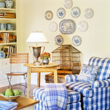 Several flea-market finds work together to create a cozy cottage space. A trophy-turned-lamp, a French bistro chair, and an old birdcage add substance and character. Mismatched dishes are turned into wall art. Soft yellow walls and touches of blue envelop the decidedly Country French room.