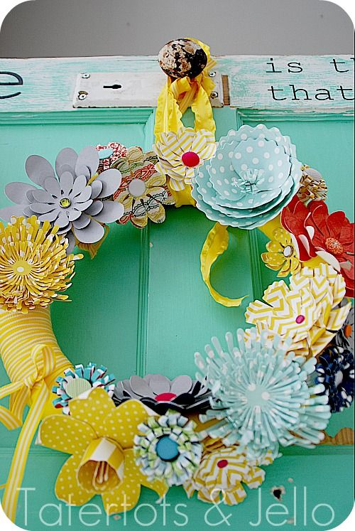 Bring in spring with this festive spring wreath. Start with a wreath form and wrap with bright ribbon or yarn. Next, pick out an array of scrap book paper and make different size and shapes flowers to place around your wreath and voila! Bring on spring!