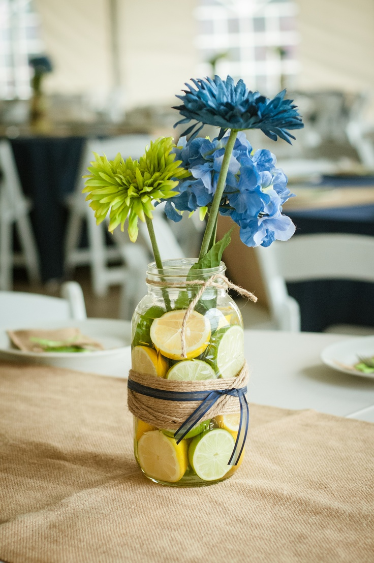 Centerpiece - Large Mason Jar $3 at Michael's or Hobby Lobby, silk hydrangea and mum $2 a stem, jute wrap and piece of ribbon plus 4 lemons/limes $5.  Right at $15 a table - much better than florist purchased centerpieces and fun and easy to make!  The night before the wedding we added halved lemons and limes and filled the jar with water.  The fruit absorbed some of the water - plumping them up!