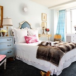 Sara Tuttle Interiors: Amazing bedroom with watery blue walls paint color, white & blue vinyl headboard, white scalloped bedding with pink trim, mismatched nightstands: blue French chest, gold console table, pink ikat pillow, faux fur throw, antique brass lamps, gold leaf framed mirror and blue silk curtains.