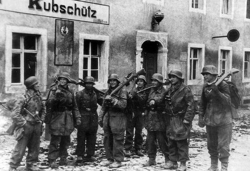 "German snipers from the Parachute Panzer Division ""Hermann Goering"" on the streets of the city Bautzen in Saxony, Germany. The man 3rd from right carries a Soviet Mosin Nagant PU sniper rifle."