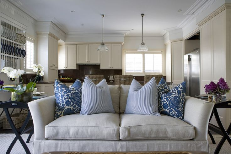 Open concept living room kitchen. Blue white decorative pillows on off white couch sofa. http://cococozy.com
