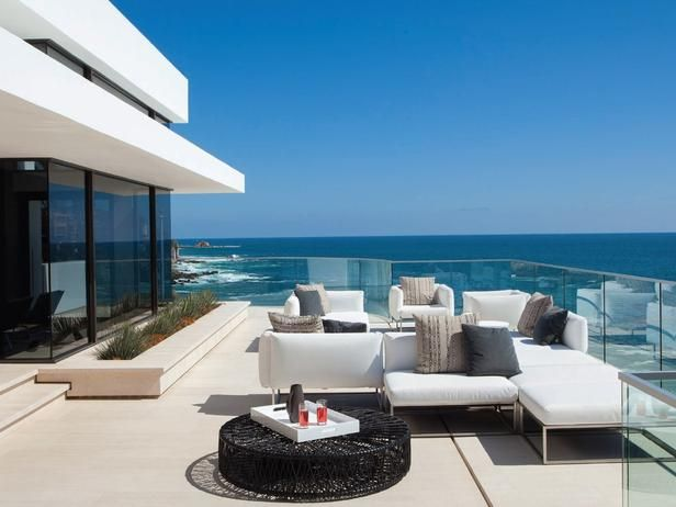 A modern white sofa echoes the cream limestone in this contemporary outdoor space. The airy feeling is complemented by the glass railing that enhances an uninterrupted view of the water.