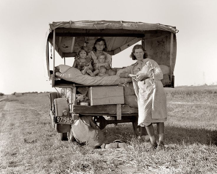 """August 1936. Family between Dallas and Austin, Texas. The people have left their home and connections in South Texas, and hope to reach the Arkansas Delta for work in the cotton fields. No food and three gallons of gas in the tank. The father is trying to repair a tire. Three children. Father says, """"It's tough but life's tough anyway you take it."""""""