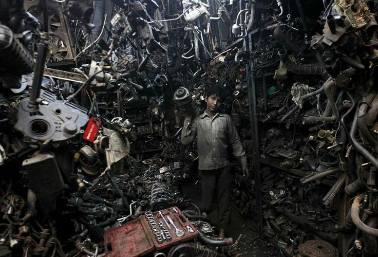 Abdul Samad, 13, carries a part of a used car engine inside an automobile workshop in Mumbai, India, on July 10, 2012. An Indian automobile industry body on Tuesday slightly lowered its car sales growth forecast for the year ending next March, as higher costs and slower economic expansion impinge on demand. Photo Danish Siddiqui / Reuters