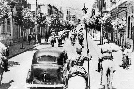 The fall of Damascus to the Allies, late June 1941. A car carrying the Free French commanders, General Georges Catroux and Major-General Paul Louis Le Gentilhomme, enters the city. They are escorted by Vichy French Circassian cavalry