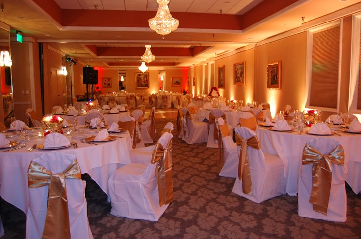 Gold uplighting with a little bit of red wedding decor for Wedding reception bathroom ideas