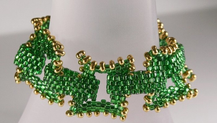 May's birthstone is Emerald.  I used Miyuki 10/0 Triangle beads to create open wavy rectangles and accented them with gold plated Miyuki Berry beads.  Instructions for this design are in the two part YouTube video:  http://youtu.be/00h791nUeIQ  http://youtu.be/K51Uyada92g
