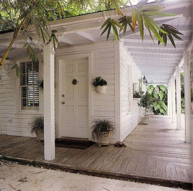 small concrete cottage with wrap around verandah in housz