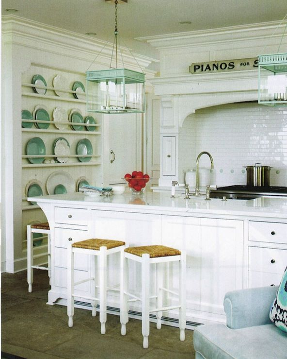 white kitchen cabinets, kitchen island, turquoise blue lanterns, white seagrass counter stools, sink in kitchen island, glossy subway tiles backsplash, turquoise blue decorative plates and polished nickel goose neck faucet.