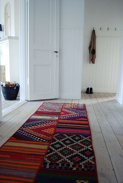 Colorful ethnic rugs in pure, white, uncluttered space