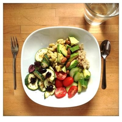 bowl filled with quinoa, avocado, cucumber, tomatoes, zuccini, black ...