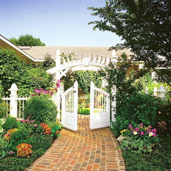 A cheery gate and classic brick path make for a stunning entry. More garden inspiration: http://www.bhg.com/gardening/design/styles/features-that-create-an-outstanding-garden/?socsrc=bhgpin090412brickgardenpath#page=3