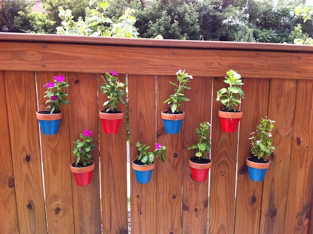 Hang potted flowers on fence